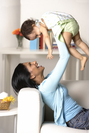 indian subcontinent ethnicity: woman holding baby in the air