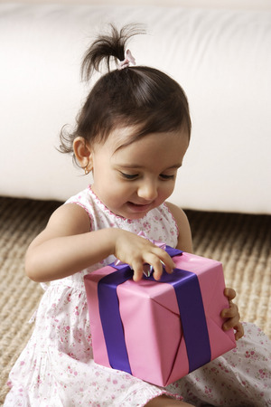 toddler girl opening present Stock Photo