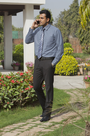 India, Businessman walking in garden and talking on mobile phone