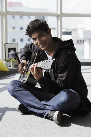 young man sitting on ground playing a guitar