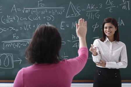 writing western: Adult student raising hand for teacher