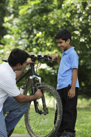 Father and son fixing bike together