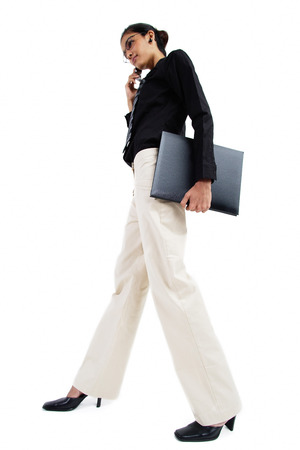 Business woman with mobile phone, carrying folder, low angle view