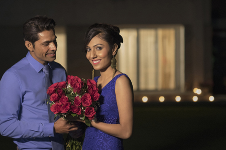 evening wear: woman and man with red roses in evening wear at night