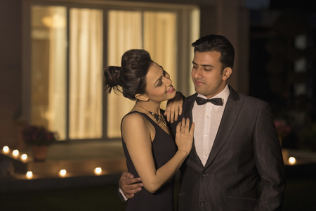 evening wear: Man and woman in evening wear embracing