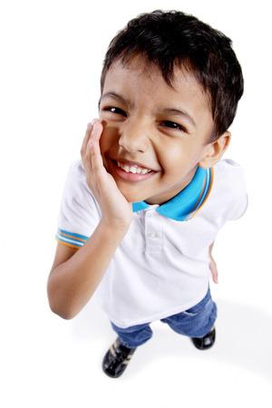 Young boy looking up at camera, hand on chin