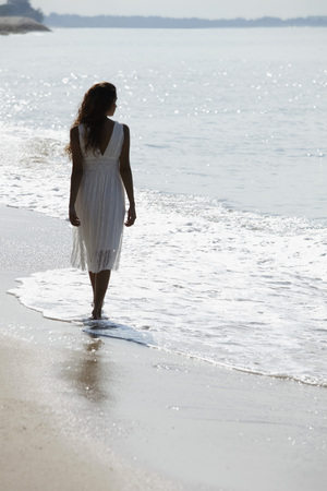 back view of woman wearing white dress and walking along the beach 版權商用圖片