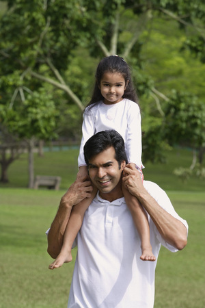3 4 years: A father carries his daughter on his shoulders as they both look at the camera LANG_EVOIMAGES