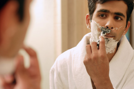Man shaving his face, looking in mirror