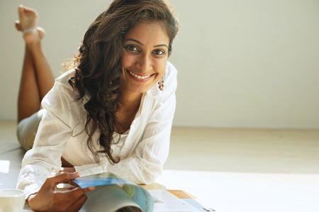 Woman smiling at camera, flipping through magazine
