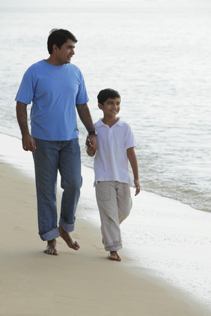 Father and son holding hands and walking down the beach.