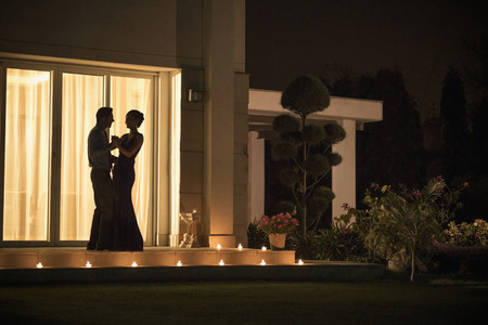 evening wear: Man and woman in evening wear dancing outside at night LANG_EVOIMAGES