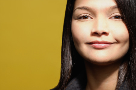 yellow  ochre: Young woman against yellow background, head shot