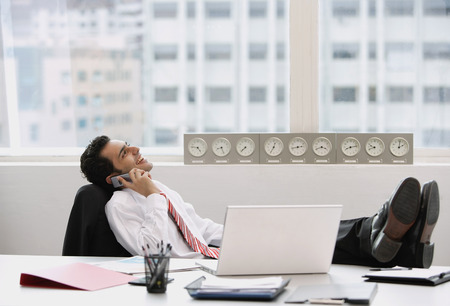 wasting away: Businessman in office, using mobile phone, feet up on desk