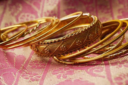 indoor shot: gold Indian bangles on pink sari cloth LANG_EVOIMAGES
