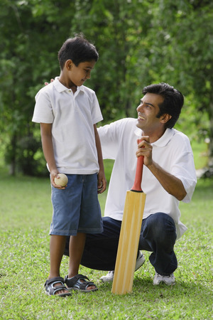 A father and son play cricket together
