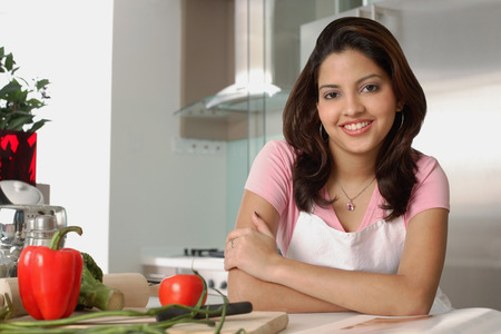 Woman sitting in kitchen, smiling at camera