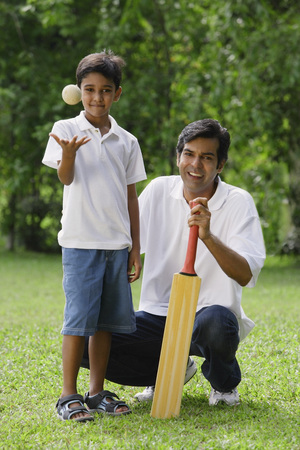 A father and son look at the camera as they play cricket together Reklamní fotografie