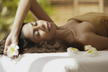 A woman lying down with frangipani flowers around her