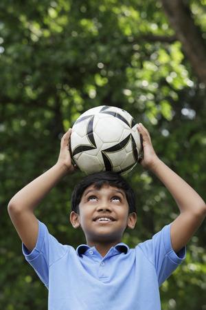Young boy balances ball on his head