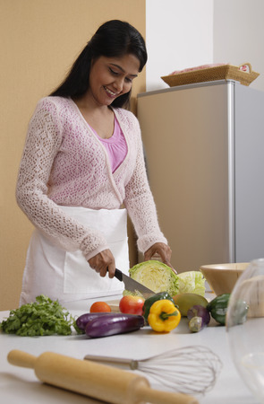 Indian woman cutting vegetables in the kitchen LANG_EVOIMAGES
