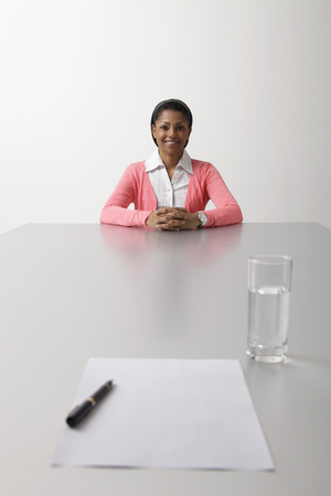 young woman sitting on end of the table waiting to be interviewed LANG_EVOIMAGES