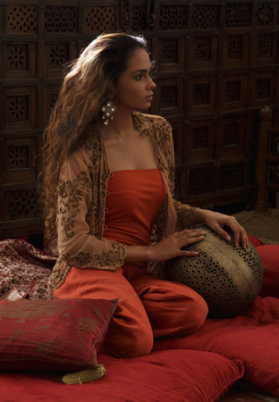 traditionally indian: Young woman relaxing on pillows with Indian antiques LANG_EVOIMAGES