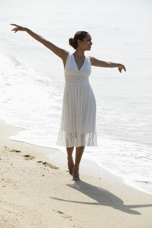 young woman with arms out stretched walking along the beach