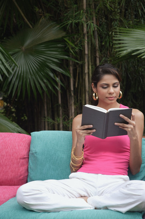 Woman of sofa reading book outdoors