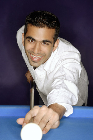 Young man playing pool, smiling at camera LANG_EVOIMAGES