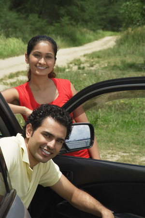 20 23 years: Young couple with car smiling at camera
