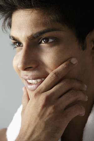 head shot of young man holding his chin and smiling