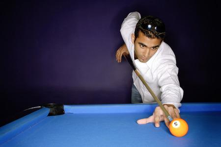 bola de billar: Young man preparing to hit pool ball LANG_EVOIMAGES