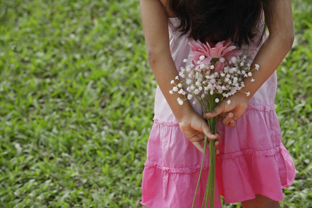 3 4 years: A small girl holds flowers behind her back
