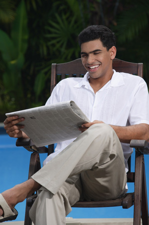 only 1 person: Man sitting in chair by the pool, reading a newspaper