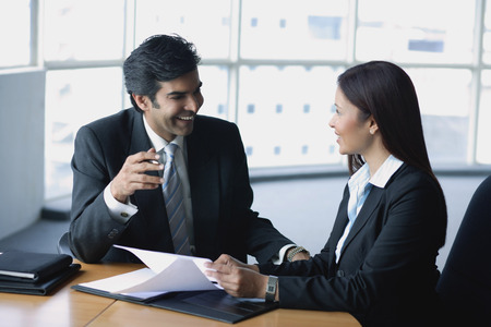 together with long tie: Businessman and businesswoman in office, having a discussion LANG_EVOIMAGES