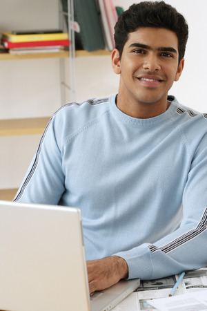 Young man with laptop smiling at camera