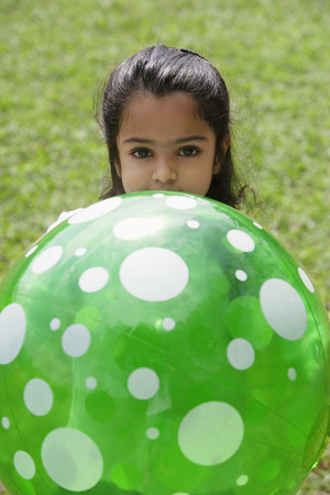 A small girl plays with a green ball