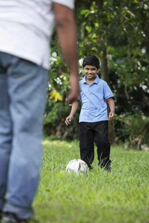 one parent: Young boy kicking ball to his father
