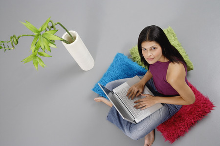 Woman sitting on floor with laptop, looking up at camera
