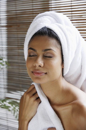 Indian woman closing her eyes relaxing with towel on her head