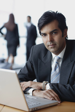 Businessman sitting in front of laptop, looking at camera Stock Photo