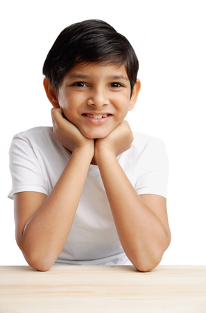 chin on hands: Boy with hands on chin, smiling
