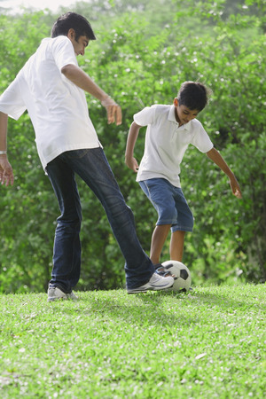 A father and son play soccer together