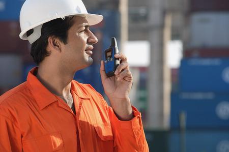 only 1 person: Man in work uniform using walkie talkie