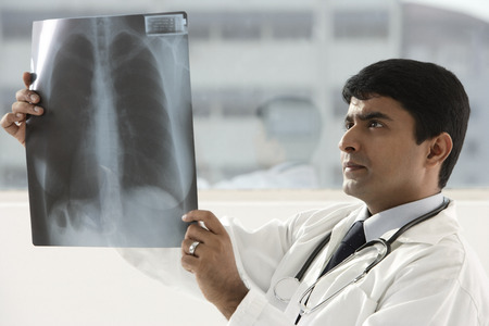 indian doctor holding up x-ray scan Stock Photo - 69404780
