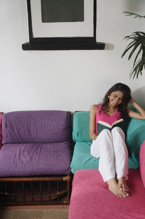 Woman sitting on sofa, reading a book