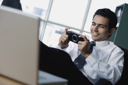 wasting away: Young businessman playing Portable game