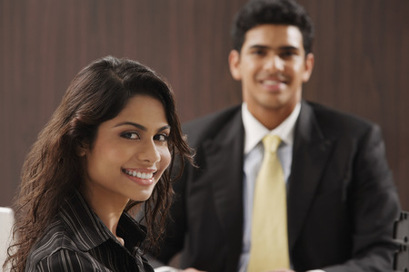 Businessman and woman smiling at camera LANG_EVOIMAGES