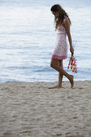 only young women: young woman walking on beach holding pink flowers